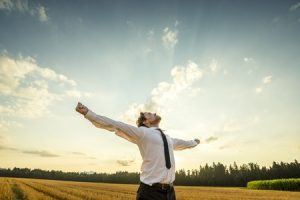43008837 - half body shot of a thankful young businessman looking up the sky with wide open arms, standing at the open field.